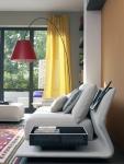 El mueble y el puff en los mismos tonos aportan calidez a esta sala, en la que se destaca la lámpara, más moderna, en colores rojo y negro, que juegan armoniosamente con la cortina, la alfombra y la pared naranja.
