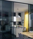 La cortina amarilla se convierte en la protagonista de esta cocina, de estilo moderno. Las puertas corredizas de vidrio oscuro hacen las veces de un separador de ambientes y a su vez integran esta área con la del comedor.
