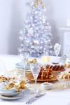 Los detalles en color dorado se convierten en los protagonistas de esta mesa, en la que las velas lucen espléndidas y crean una atmósfera acogedora. De fondo: el árbol, hecho de cristales, con destellos ligeramente dorados, da contraste al rincón.