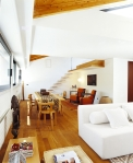 La madera en tono caramelo es una estrella indiscutible del área del comedor, donde se aprecia una decoración ecléctica, que combina detalles modernos y étnicos. El gran ventanal ilumina todo el lugar, en el que resaltan las butacas en tono naranja, debajo de la escalera.