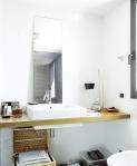 El cuarto de baño se convierte en un área sencilla y acogedora por detalles como la canasta de ratán debajo del lavamanos, el que presenta un diseño moderno en tono blanco. El mesón aporta calidez al espacio.