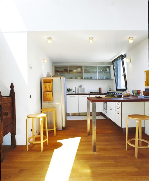 Los detalles niquelados de la cocina logran un equilibrio fabuloso con los toques de madera en los pisos y taburetes. ¿Otro protagonista de este espacio? La luz que ingresa desde el ventanal.