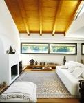 El tono blanco del sofá y las paredes juega a la perfección con la alfombra y los detalles en madera del techo, el piso y la mesa baja del fondo.