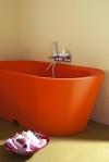Una bañera que además de ser funcional, se convierte en un elemento decorativo del cuarto de baño gracias al impactante color naranja. La bandeja con las toallas y productos dan un toque cálido al ambiente.