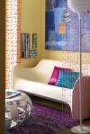 Esta pequeña sala se transforma en un lugar realmente acogedor, donde los detalles como los cojines, las cuentas que dividen el espacio, el cuadro y la alfombra invaden de color toda el área.