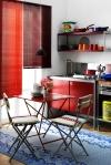 La cocina es otro espacio en el que el color es el protagonista. Utilizado en sillas, persianas y anaqueles, el rojo contrasta perfectamente con la alfombra en tono turquesa.