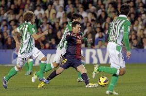 Messi supera récords con la misma facilidad que defensas rivales. En la imagen, el argentino lleva el balón rodeado de jugadores del Betis, en el partido de Liga disputado en el estadio Benito Villamarín de Sevilla.