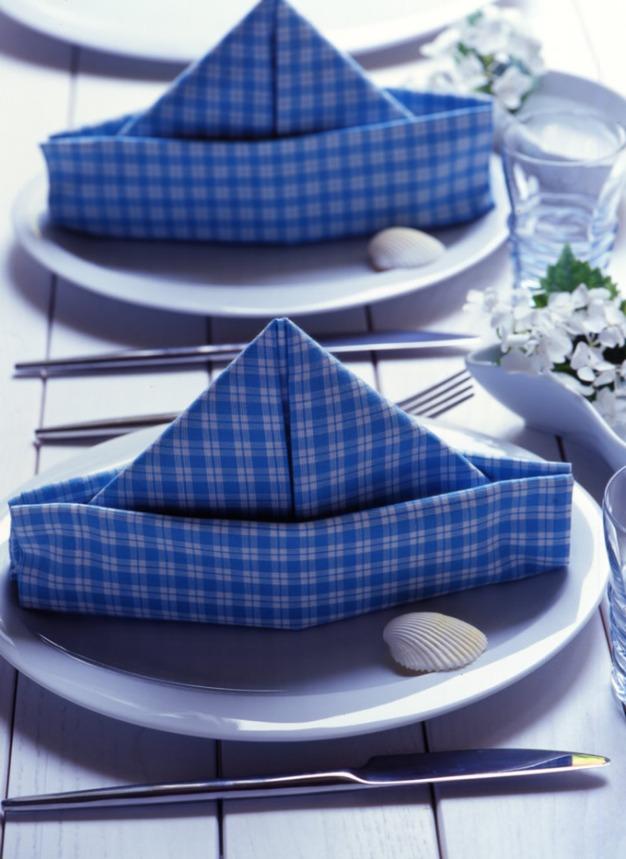 ¡Sea ingeniosa! Coloque las servilletas, dobladas en forma de barquitos, sobre los platos. ¿Otro complemento? Flores blancas en pequeños envases a lo largo de la mesa. Logrará un ambiente fresco y novedoso.