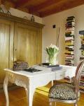 Una mesa de estilo clásico logra un contraste armonioso con la silla –también clásica– de tapiz animal print, en este espacio de trabajo. El mueble de madera y los libros logran una composición perfecta en esta área.