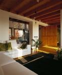 Una vista de la sala en la que se han usado colores neutros, como el blanco y el negro, para complementarlos con pequeños detalles, como los cojines en tono verde y las plantas en la mesa de centro y a un costado del sofá. La puerta de madera en el fondo forma parte de la decoración de este espacio.