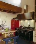 Se ha logrado aprovechar la cocina (tipo americana) como un lugar que forma parte del área social del departamento. El mueble de madera, los detalles niquelados, la refrigeradora en color rojo y las sillas azules se conjugan para crear un espacio cálido y muy funcional.