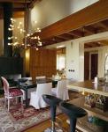 El comedor muestra una mezcla fantástica de estilos en la que resalta la silla Luis XVI, en madera a la que se la dado un tono plata, combinada perfectamente con el tapiz en tonos rojos y plateado. La alfombra aporta calidez al lugar, así como la lámpara y los detalles sobre la mesa de vidrio. Las demás sillas, con diseño más lineal, dan un toque moderno al sitio. Asimismo, las sillas tipo bar de la cocina se integran al espacio.