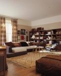 Otra vista de la sala, en la que se aprecian los puff con tapices de diferentes diseños. La pared terracota del costado y los cuadros aportan personalidad al ambiente.