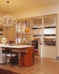 En el comedor se destaca la lámpara con un estilo chandelier moderno. Este da paso a la cocina, donde los detalles mantienen los mismos tonos del comedor y a la que se accede gracias a la puerta de madera y vidrio.