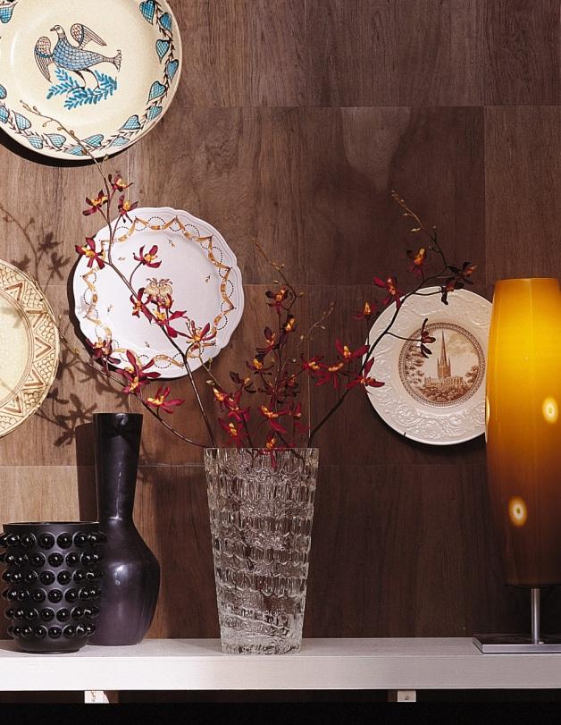 Platones de fina cerámica, jarrones, una moderna lámpara y la pared con enchape en madera crean un rincón ecléctico y de buen gusto.