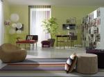 Una vista del lugar en el que se destaca el puff hecho en madera, combinado con otro en tapiz en tono morado. La alfombra luce el mismo diseño de rayas del cojín. Al fondo se aprecian las lámparas chinas de papel.