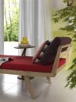 Un mueble tipo canapé elaborado en madera, con un tapiz rojo que logra una fantástica combinación con los colores de los cojines. La mesa de madera y la planta complementan de manera fabulosa este rincón, ideal para la lectura.