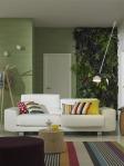 La pared verde y las plantas logran un marco perfecto para el mueble blanco de la sala. Sobre este se aprecian los almohadones con diseños de rayas y dots en tonos brillantes. La pequeña mesa de centro, también en madera, y la lámpara de pie, aportan un toque moderno al espacio.