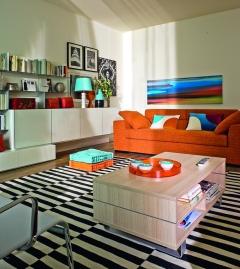 La decoración en blanco y negro de esta sala logra un dinámico contraste con los colores turquesa y naranja de algunos detalles. El sofá se convierte en un protagonista del área y la mesa pasa a ser un elemento funcional, donde se pueden colocar libros en los compartimentos inferiores.