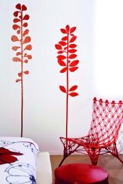 La pared blanca del dormitorio adquiere un dinamismo especial con estos stickers, la silla y la mesita… Todo en un tono rojo brillante.