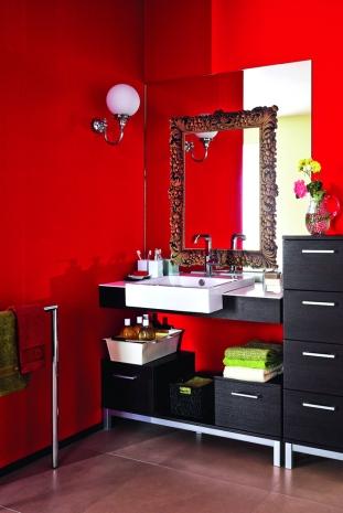 El mueble del baño, elaborado en un elegante wengue y complementado por detalles como el espejo con un sticker de marco antiguo, luce fabuloso sobre esta pared roja, que además de lograr un acertado impacto, da vida y contraste al espacio.