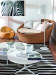 El blanco y el negro se imponen en esta decoración, en la que los elementos se conjugan a la perfección entre sí. El mueble de ratán y la alfombra a rayas son los protagonistas del espacio, en el que sea aprecian las delicadas mesas bajas y los adornos en tono blanco.