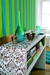 Otro ejemplo de elementos que logran un ambiente acogedor es esta pared con papel tapiz a rayas que combina los colores verde y turquesa. En esta área se aprecia la consola en tonos blanco y café, que juegan a la perfección con los adornos turquesa y bronce que están sobre ella.